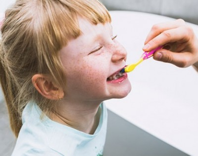 At what age should babies start brushing their teeth?